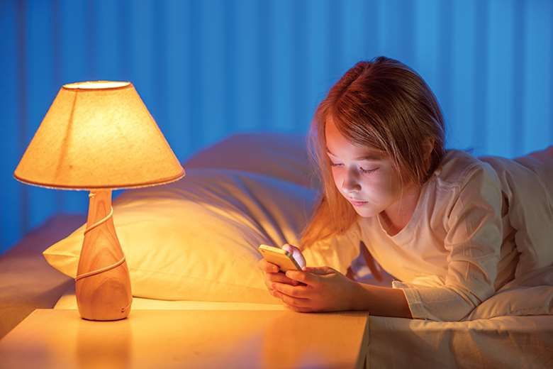 The Royal College of Paediatrics and Child Health recommends banning screens in the hour before bedtime. Picture: Realstock1/Adobe Stock